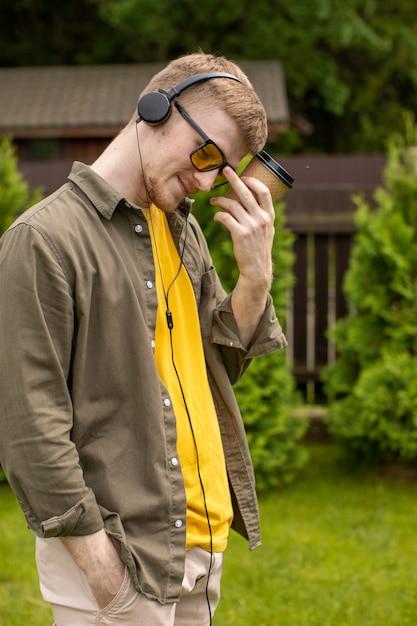 Portret Młodego Brodatego Faceta W żółtych Okularach I żółtej Koszulce Niedbale Ubranego Stojącego Z Jednorazowym Kubkiem Papierowym W Zamyśleniu Słuchania Muzyki Online Przez Słuchawki Na Zielonym Tle Premium Zdjęcia
