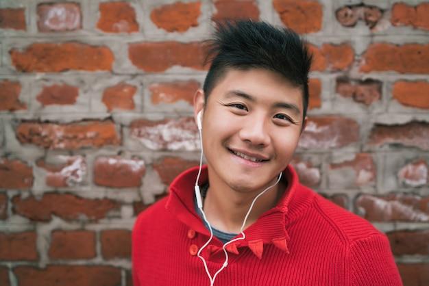 Portret Młodego Chłopca Azjatyckich Słuchanie Muzyki Przez Słuchawki Na Zewnątrz ściany Z Cegły. Koncepcja Miejska. Darmowe Zdjęcia