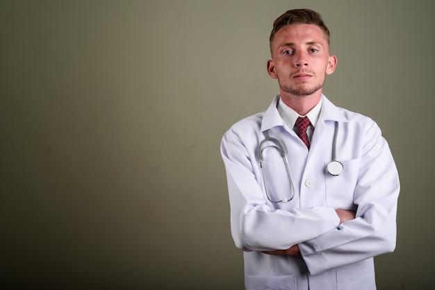 Portret Młodego Lekarza Człowieka Przed Kolorową ścianą Premium Zdjęcia
