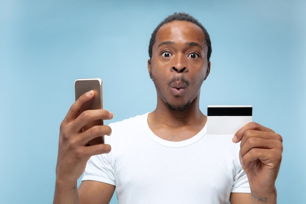 Portret Młodego Mężczyzny Afro-amerykańskiego W Białej Koszuli, Trzymając Kartę I Smartfon. Darmowe Zdjęcia