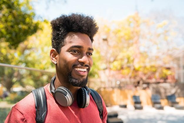 Portret Młodego Mężczyzny Afro, Ciesząc Się I Słuchając Muzyki W Słuchawkach. Koncepcja Technologii I Stylu życia. Premium Zdjęcia