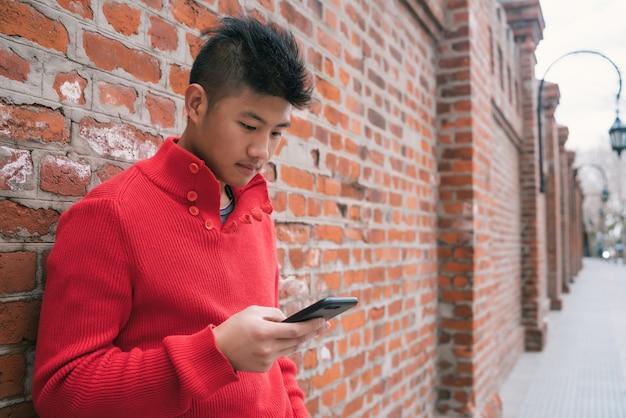Portret Młodego Mężczyzny Azji Przy Użyciu Swojego Telefonu Komórkowego Na Zewnątrz ściany Z Cegły. Koncepcja Komunikacji. Darmowe Zdjęcia