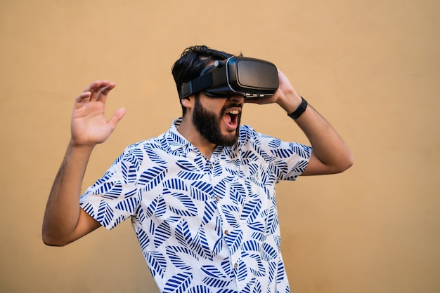 Portret Młodego Mężczyzny Bawiącego Się Okularami Vr-zestaw Wirtualnej Rzeczywistości Przeciw żółtej Przestrzeni. Urządzenie Okularów Vr. Koncepcja Technologii. Darmowe Zdjęcia