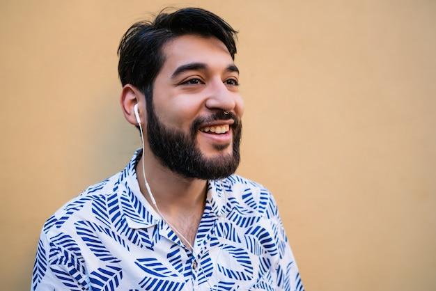 Portret Młodego Mężczyzny łacińskiej Na Sobie Letnie Ubrania I Słuchanie Muzyki W Słuchawkach Przeciw żółtej Przestrzeni. Darmowe Zdjęcia