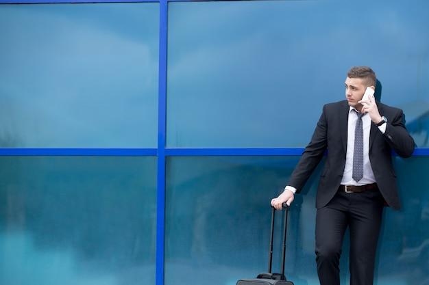 Portret Młodego Podróżującego W Garniturze Stały Z Walizką I Nawiązaniem Połączenia. Skopiuj Miejsce Darmowe Zdjęcia