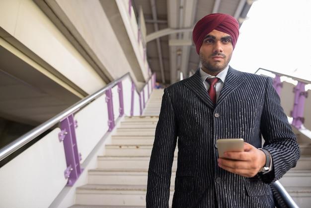 Portret Młodego Przystojnego Indyjskiego Biznesmena Sikhów W Turbanie Podczas Zwiedzania Miasta Bangkok, Tajlandia Premium Zdjęcia
