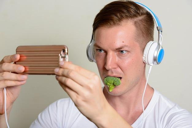 Portret Młodego Przystojnego Mężczyzny Ze Słuchawkami, Jedzenie Brokułów I Przy Selfie Premium Zdjęcia