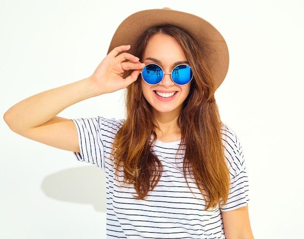 Portret Młodego Stylowego Modelu Roześmiany Kobieta W Letnie Ubrania W Brązowy Kapelusz Na Białym Tle Na Białej ścianie Darmowe Zdjęcia