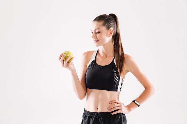 Portret Młodego Uśmiechniętego Sportwoman Gospodarstwa Zielone Jabłko Darmowe Zdjęcia