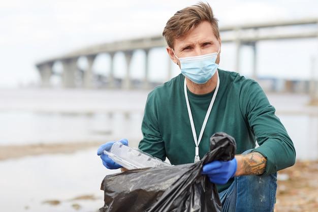 Portret Młodego Wolontariusza W Masce Ochronnej, Wkładanie śmieci Do Torby I Patrząc Na Kamery Na Zewnątrz Premium Zdjęcia