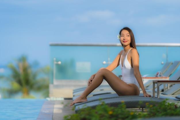 Portret Młodej Azjatykciej Kobiety Szczęśliwy Uśmiech Relaksuje Wokoło Pływackiego Basenu W Hotelowym Kurorcie Darmowe Zdjęcia