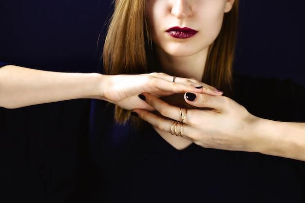 Portret Młodej Dorosłej Białej Kobiety Na Sobie Ciemną śliwkową Szminkę I Trzymając Ręce Z Ciemnym Manicure Razem Przed Jej Szyją. . Premium Zdjęcia