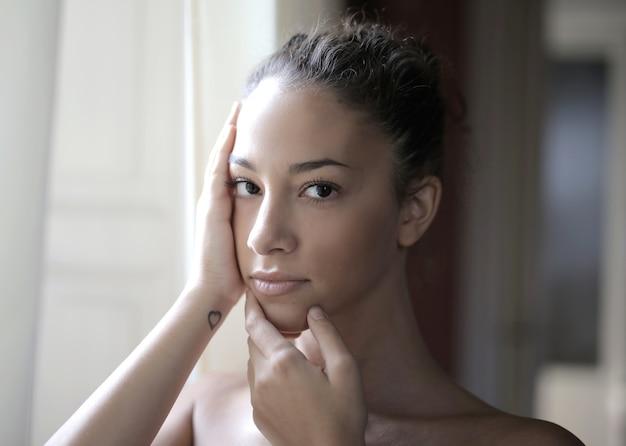 Portret Młodej Dziewczyny Atrakcyjne Z Rękami Na Twarzy, Pozowanie Przed Oknem Darmowe Zdjęcia