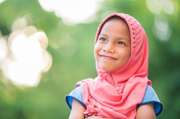 Portret Młodej Dziewczyny Muzułmańskiej, Pokryte Czerwonym Suknem, Uśmiechnięty, Szczęśliwy I Kopiować Miejsca Premium Zdjęcia