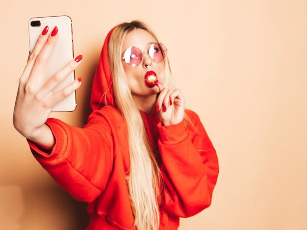 Portret Młodej Dziewczyny Piękne Hipster Zły W Modne Dżinsy Ubrania I Kolczyk W Nosie. Seksowny Beztroski Uśmiechający Się Blond Kobieta Bierze Selfie. Model Pozytywny Lizanie Okrągłe Cukierki Cukrowe Darmowe Zdjęcia