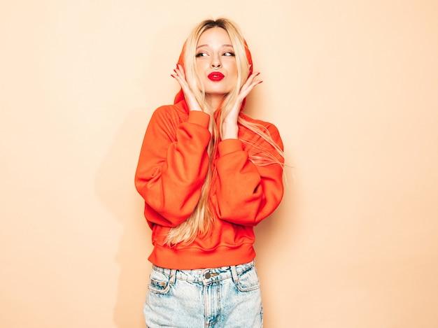 Portret Młodej Dziewczyny Piękne Hipster Zły W Modnej Czerwonej Bluzie Z Kapturem I Kolczyk W Nosie. Seksowny Beztroski Blond Kobieta Pozowanie Studio. Pozytywny Model Zabawy Darmowe Zdjęcia
