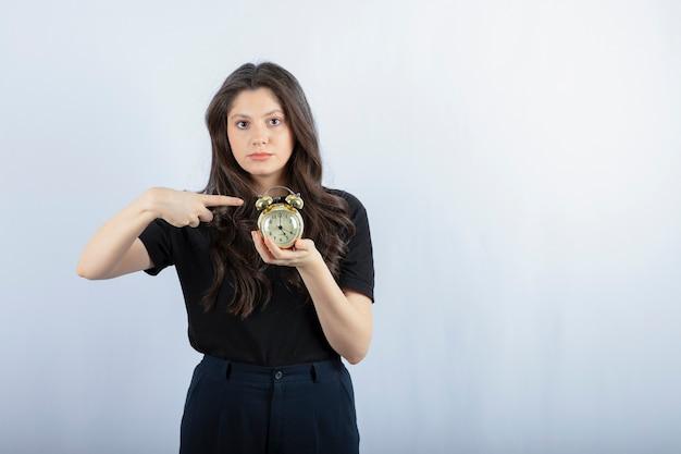 Portret Młodej Dziewczyny Z Budzikiem, Stojąc Na Szaro. Darmowe Zdjęcia