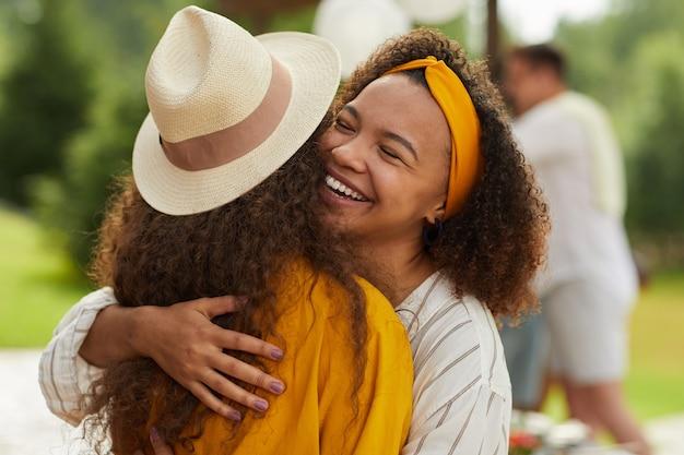 Portret Młodej Kobiety African-american Przytulanie Przyjaciela I Uśmiechnięty Radośnie, Ciesząc Się Imprezą Na świeżym Powietrzu W Lecie Premium Zdjęcia