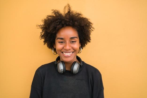 Portret Młodej Kobiety Afro American Patrząc Pewnie I Nosząc Czarne Słuchawki Na żółtym Tle. Premium Zdjęcia