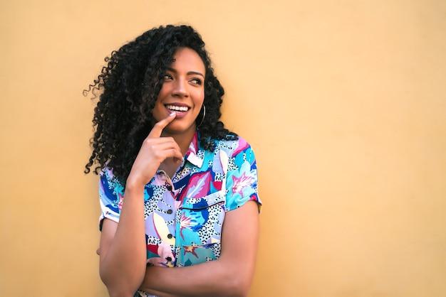 Portret Młodej Kobiety Afro Amerykański Wyglądający Pewnie I Pozujący Na żółtym Tle. Premium Zdjęcia