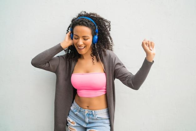 Portret Młodej Kobiety Afro, Ciesząc Się I Słuchając Muzyki Z Niebieskimi Słuchawkami. Koncepcja Technologii I Stylu życia. Premium Zdjęcia