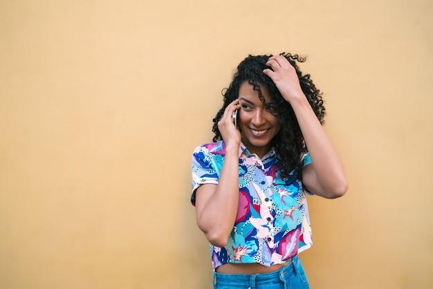 Portret Młodej Kobiety Afro Rozmawia Przez Telefon Na żółtym Tle. Koncepcja Komunikacji. Premium Zdjęcia