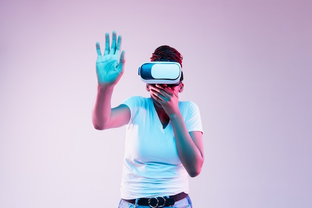 Portret Młodej Kobiety Afroamerykanów W Okularach Vr W świetle Neonu Na Gradientowym Tle. Pojęcie Ludzkich Emocji, Wyrazu Twarzy, Nowoczesnych Gadżetów I Technologii. Coś Dotyka. Darmowe Zdjęcia