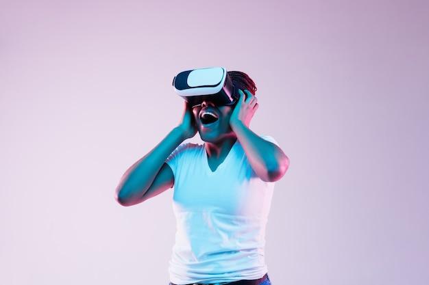 Portret Młodej Kobiety Afroamerykanów W Okularach Vr W świetle Neonu Na Gradientowym Tle. Pojęcie Ludzkich Emocji, Wyrazu Twarzy, Nowoczesnych Gadżetów I Technologii. Spójrz Zdziwiony. Darmowe Zdjęcia