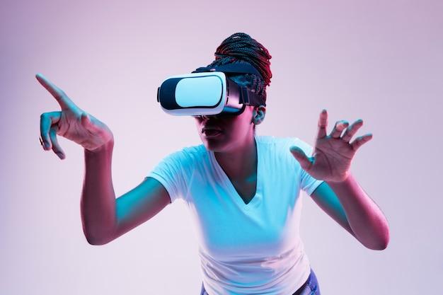 Portret Młodej Kobiety Afroamerykanów W Okularach Vr W świetle Neonu Na Gradientowym Tle. Pojęcie Ludzkich Emocji, Wyrazu Twarzy, Nowoczesnych Gadżetów I Technologii. Wskazując. Darmowe Zdjęcia