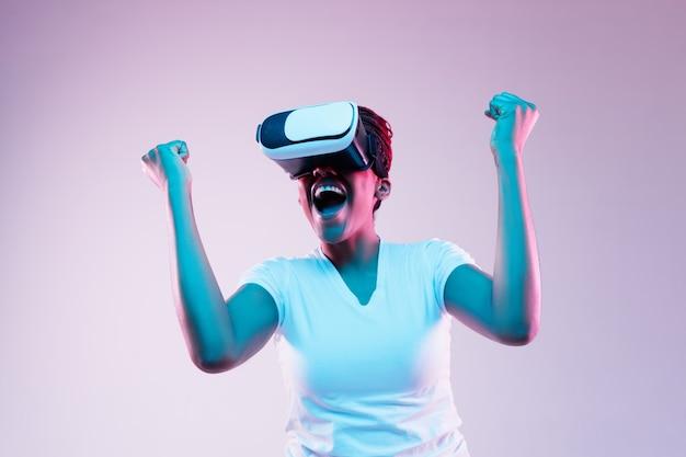 Portret Młodej Kobiety Afroamerykanów W Okularach Vr W świetle Neonu Na Gradientowym Tle. Pojęcie Ludzkich Emocji, Wyrazu Twarzy, Nowoczesnych Gadżetów I Technologii. Wygląda Na Zwycięzcę. Darmowe Zdjęcia
