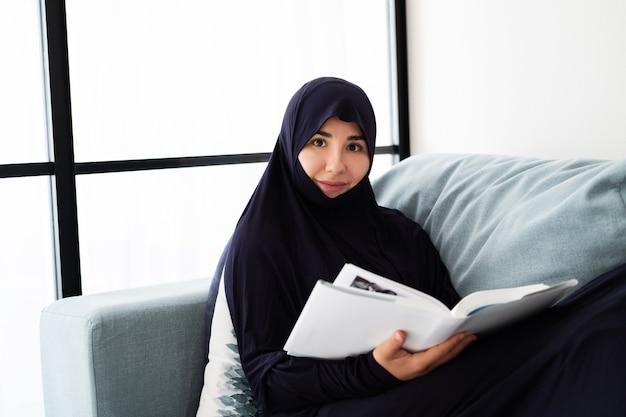 Portret Młodej Kobiety Azjatyckie Noszenie Hidżabu, Czytać Książkę W Domu Premium Zdjęcia