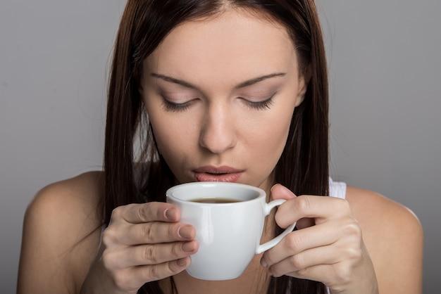 Portret młodej kobiety, która pije kawę. Premium Zdjęcia
