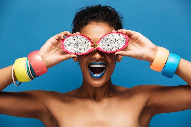Portret Młodej Kobiety Mulat Z Bransoletami Na Ramionach, Zabawy Obejmujących Oczy Z Dojrzałych Owoców Pitahaya Pokroić Na Pół, Odizolowane Na Niebiesko Darmowe Zdjęcia