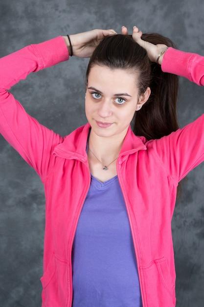 Portret młodej kobiety na szarej ścianie Premium Zdjęcia