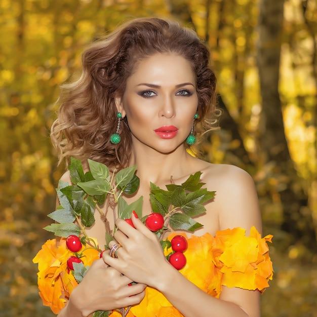 Portret Młodej Kobiety Piękne W Sukience Z Liści Jesienią W Parku W Sezonie Jesiennym Z Bukietem Kwiatów W Dłoniach. Zdjęcie Artystyczne Premium Zdjęcia