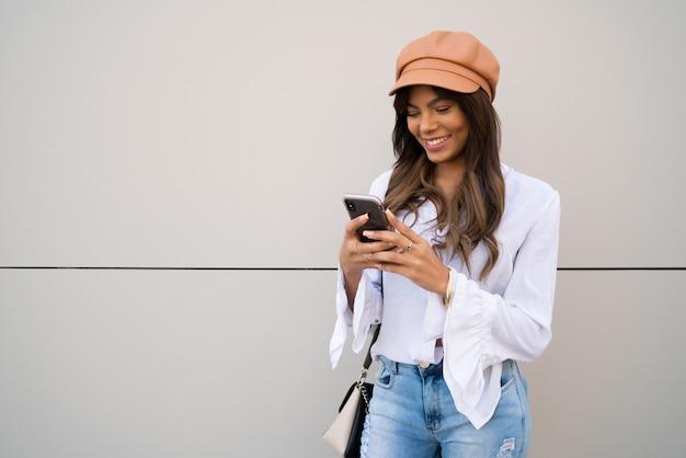 Portret Młodej Kobiety Przy Użyciu Swojego Telefonu Komórkowego, Stojąc Na Zewnątrz Na Ulicy Darmowe Zdjęcia