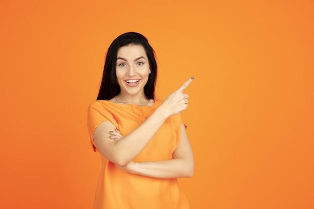 Portret Młodej Kobiety Rasy Kaukaskiej Na Pomarańczowym Tle Studio. Piękna Brunetka Modelka W Koszuli. Pojęcie Ludzkich Emocji, Wyraz Twarzy, Sprzedaż, Reklama. Copyspace. Wskazując, Pokazując, Uśmiechając Się. Darmowe Zdjęcia