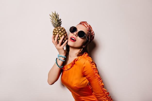 Portret Młodej Kobiety W Okularach Przeciwsłonecznych I Pomarańczowej Bluzce Z Ananasem Na Odosobnionej Przestrzeni. Darmowe Zdjęcia