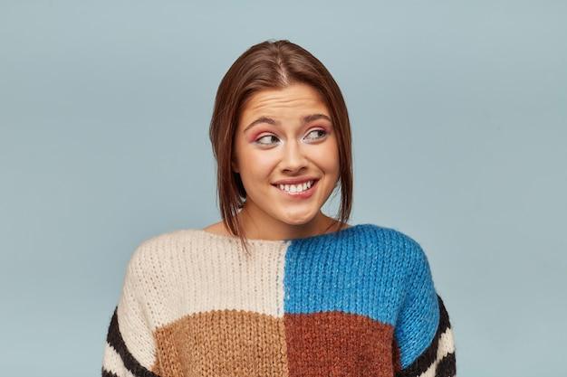 Portret Młodej Kobiety W Wielobarwnym Swetrze Czuje Się Winna Z Niepokojem Patrzy W Bok, Przygryzła Wargę Darmowe Zdjęcia