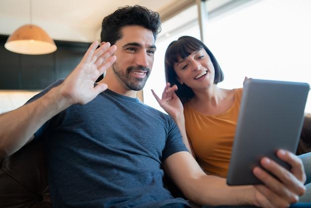 Portret Młodej Pary Na Rozmowę Wideo Z Cyfrowym Tabletem, Siedząc Na Kanapie W Domu Premium Zdjęcia