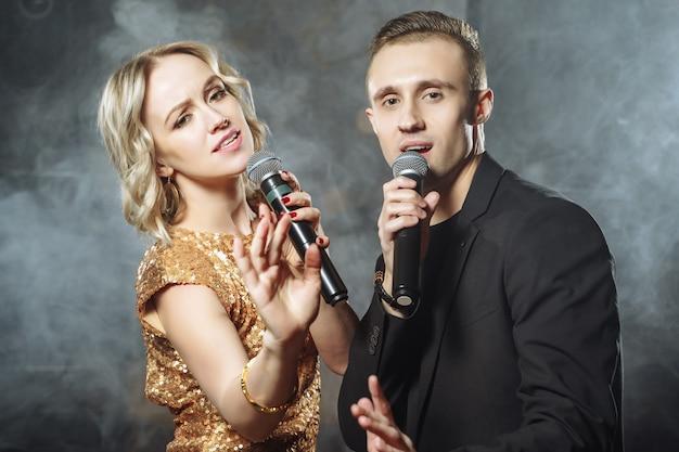 Portret młodej pary z mikrofonami Premium Zdjęcia