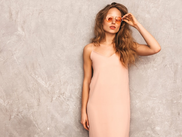 Portret Młodej Pięknej Dziewczyny Uśmiechający Się W Modne Letnie światło Różowa Sukienka. Seksowny Beztroski Kobiety Pozować. Pozytywny Model Zabawy W Okrągłych Okularach Przeciwsłonecznych Darmowe Zdjęcia