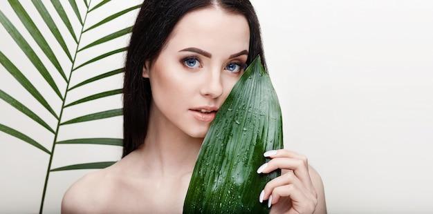 Portret Młodej Pięknej Kobiety O Zdrowej Gładkiej Skórze Trzyma Zielony Tropikalny Liść Premium Zdjęcia