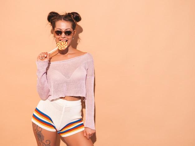 Portret Młodej Pięknej Seksownej Kobiety Uśmiechający Się Z Fryzura Ghul. Modna Dziewczyna W Codziennych Letnich Ubraniach W Okularach Przeciwsłonecznych. Gorący Model Na Beżu. Jedzenie, Gryzący Lizak Darmowe Zdjęcia