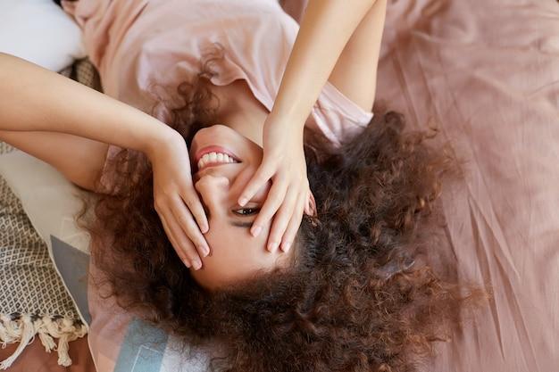 Portret Młodej Szczęśliwej Ciemnoskórej Kobiety Leżącej Na łóżku I Twarzy Z Rękami, Ciesząc Się Słonecznym Dniem W Domu I Uśmiechając Się, Spędza Wolny Dzień W Domu. Darmowe Zdjęcia
