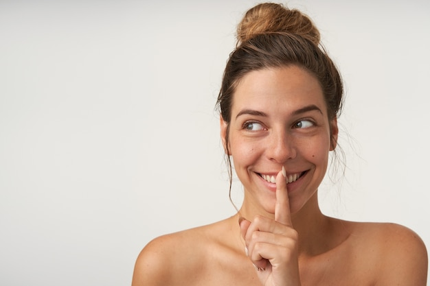 Portret Młodej Wesołej Kobiety Patrząc Na Bok Z Szerokim Uśmiechem, Udając, że Zachowuje Tajemnicę, Trzymając Palec Wskazujący W Pobliżu Ust, Na Białym Tle Darmowe Zdjęcia