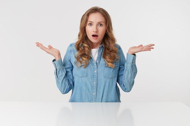 Portret Młodej Zdumionej ślicznej Kręconej Blondynki Pani W Dżinsowych Koszulach Siedzi Przy Białym Stole I Rozkłada Ręce Na Bok, Odizolowane Na Białym Tle. Darmowe Zdjęcia