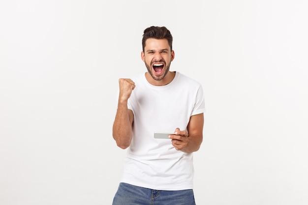 Portret młody człowiek bawić się wideo gry na telefonie komórkowym na szarość. Premium Zdjęcia