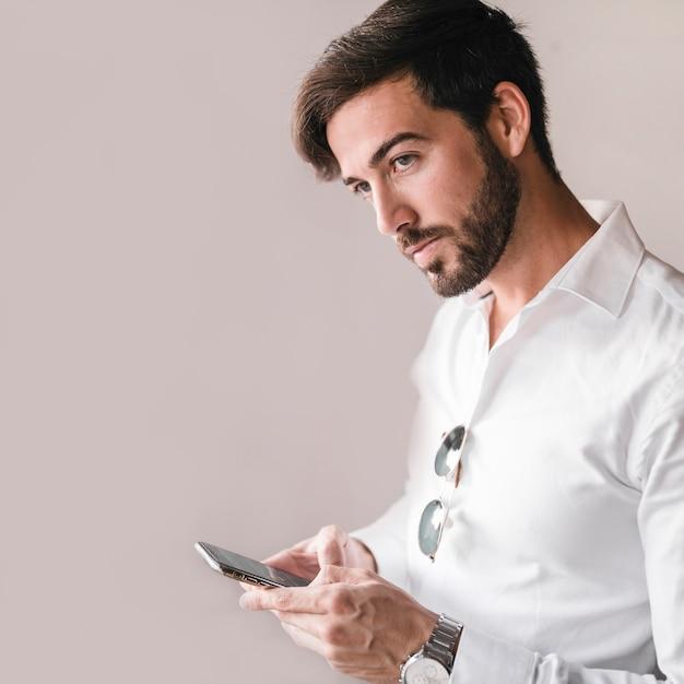 Portret młody człowiek używa smartphone Darmowe Zdjęcia