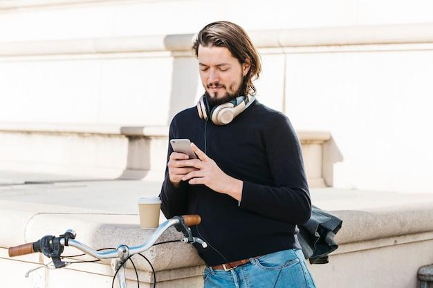 Portret młody człowiek z hełmofonem wokoło jego szyi używać telefon komórkowego przy outdoors Darmowe Zdjęcia